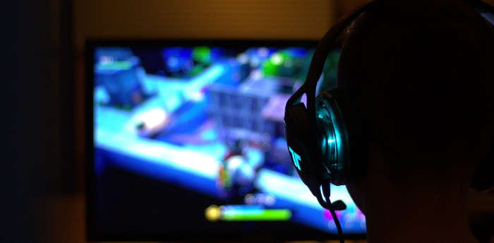 A young boy playing Fortnite on his TV